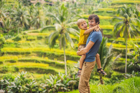 Dad and son travelers on Beautiful Rice Terraces against the background of famous volcanoes in Bali, Indonesia Traveling with children concept