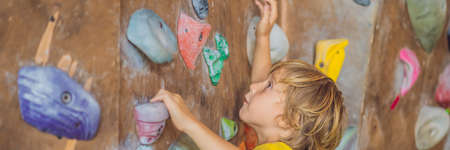little boy climbing a rock wall in special boots. indoor BANNER, LONG FORMAT