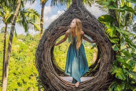 Bali trend, straw nests everywhere. Young tourist enjoying her travel around Bali island, Indonesia. Making a stop on a beautiful hill. Photo in a straw nest, natural environment. Lifestyle Reklamní fotografie
