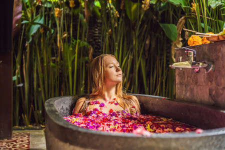 Attractive Young woman in bath with petals of tropical flowers and aroma oils. Spa treatments for skin rejuvenation. Alluring woman in Spa salon. Girl relaxing in bathtub with flower petals. Luxury