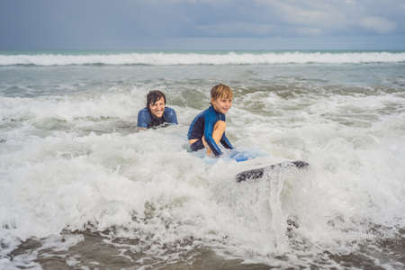 Father or instructor teaching his 5 year old son how to surf in the sea on vacation or holiday. Travel and sports with children concept. Surfing lesson for kids Reklamní fotografie