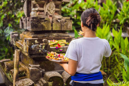 Balinese woman makes an offering to the gods