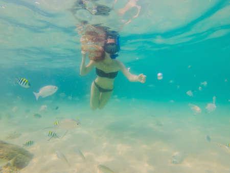 Mujer feliz en buceo con máscara de snorkel bajo el agua con peces tropicales en la piscina del mar del arrecife de coral. Estilo de vida de viaje, deportes acuáticos, aventuras al aire libre, lecciones de natación en vacaciones de verano en la playa