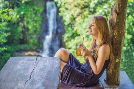 Closeup portrait image of a beautiful woman drinking ice tea with feeling happy in green nature and waterfall garden background