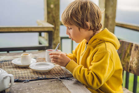 Boy drinking tea in a cafe in the mountains