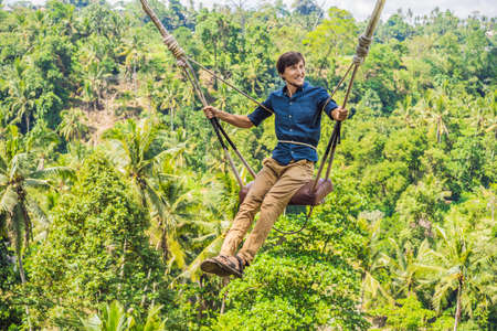 Jonge man slingeren in het regenwoud van de jungle van het eiland Bali, Indonesië. Swingen in de tropen. Schommels - trend van Bali
