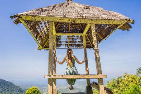 Young woman in traditional balinese gazebo. Bali island 스톡 콘텐츠