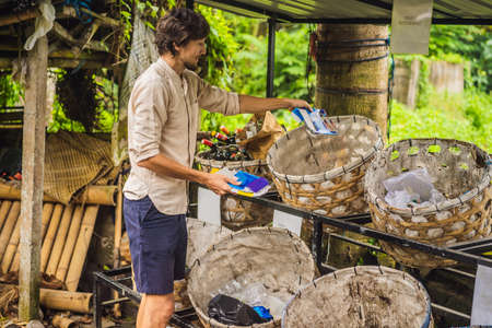 Man separately picks up trash. Separate garbage collection concept Reklamní fotografie