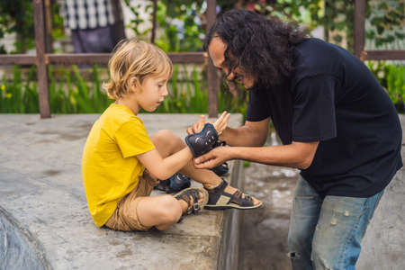 Trainer helps the boy to wear knee pads and armbands before training skate board