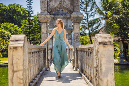 Young woman in dress in Water Palace Soekasada Taman Ujung Ruins on Bali Island in Indonesia. Amazing old architecture. Travel and holidays background