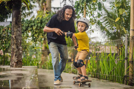 Athletic boy learns to skateboard with a trainer in a skate park. Children education, sports