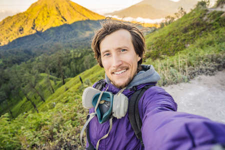 Young man tourist makes a selfie with the magnificent views on green mountains from a mountain road trecking to the Ijen volcano or Kawah Ijen on the Indonesian language. Famous volcano containing the biggest in the world acid lake and sulfur mining spot at the place where volcanic gasses come from the volcano. Tourists hike this road to meet the sunrise at the volcano
