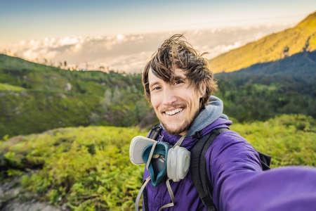 Joven turista hace un selfie con las magníficas vistas de las verdes montañas desde una carretera de montaña hasta el volcán Ijen Foto de archivo