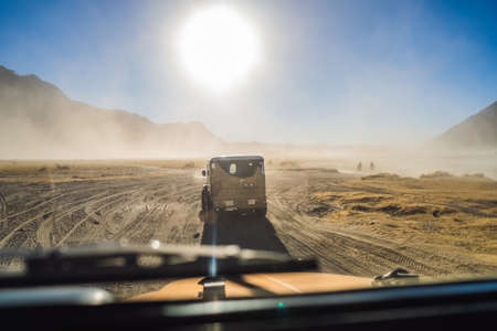 View from inside of an offroad car riding through the so-called Sea of sand inside the Tengger caldera at the Bromo Tengger Semeru National Park in the Java Island, Indonesia. One of the most famous volcanic objects in the world. Travel to Indonesia concept