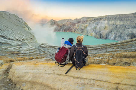 Young tourist man and woman sit at the edge of the crater of the Ijen volcano or Kawah Ijen on the Indonesian language. Famous volcano containing the biggest in the world acid lake and sulfur mining spot at the place where volcanic gasses come from the volcano. They enjoy the magnificent view on the crater Reklamní fotografie