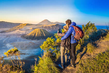 Young couple man and woman meet the sunrise at the Bromo Tengger Semeru National Park on the Java Island, Indonesia. They enjoy magnificent view on the Bromo or Gunung Bromo on Indonesian, Semeru and other volcanoes located inside of the Sea of Sand within the Tengger Caldera. One of the most famous volcanic objects in the world. Travel to Indonesia concept Reklamní fotografie