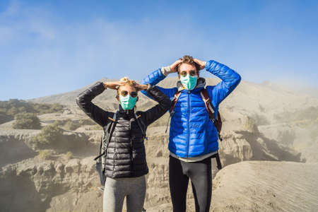 Young couple man and woman visit the Bromo volcano at the Tengger Semeru National Park on Java Island, Indonesia. They are scared of the eruption covering everything with dust and they wear safety masks to protect themselves from dangerous volcanic ash. Concept of tourists in trouble caused by a volcano