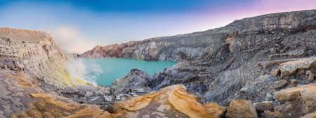 Panoramic shot of the Ijen volcano or Kawah Ijen on the Indonesian language. Famous volcano containing the biggest in the world acid lake and sulfur mining spot at the place where volcanic gasses come from the volcano