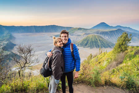 Young couple man and woman meet the sunrise at the Bromo Tengger Semeru National Park on the Java Island, Indonesia. They enjoy magnificent view on the Bromo or Gunung Bromo on Indonesian, Semeru and other volcanoes located inside of the Sea of Sand within the Tengger Caldera. One of the most famous volcanic objects in the world. Travel to Indonesia concept Фото со стока
