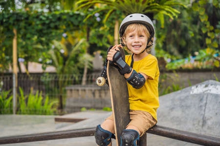 Athletic boy in helmet and knee pads learns to skateboard with in a skate park. Children education, sports Banco de Imagens