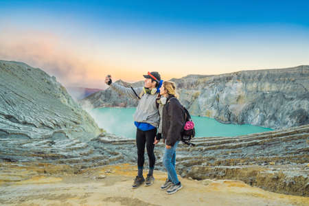 Young tourist man and woman stand at the edge of the crater of the Ijen volcano or Kawah Ijen on the Indonesian language. Famous volcano containing the biggest in the world acid lake and sulfur mining spot at the place where volcanic gasses come from the volcano. They wear respirators to protect from dangerous volcanic gasses Reklamní fotografie