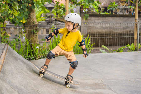 Athletic boy in helmet and knee pads learns to skateboard with in a skate park. Children education, sports Reklamní fotografie