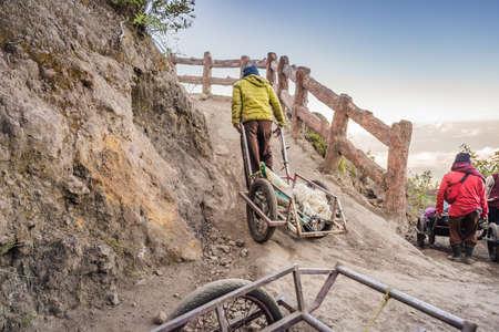 En una carretera de montaña caminando hacia el volcán Ijen o Kawah Ijen en el idioma indonesio. Famoso volcán que contiene el lago ácido más grande del mundo y un lugar minero de azufre en el lugar donde los gases volcánicos provienen del volcán. La gente local usa estos carros para llevar a los turistas cansados al volcán o traerlos de regreso