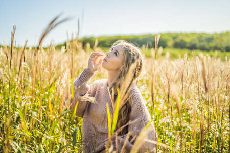 Young beautiful woman in autumn landscape with dry flowers, wheat spikes. Fashion autumn, winter. Sunny autumn, Cozy autumn sweater. fashion photo