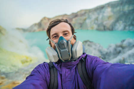 Young man tourist makes a selfie standing at the edge of the crater of the Ijen volcano or Kawah Ijen on the Indonesian language. Famous volcano containing the biggest in the world acid lake and sulfur mining spot at the place where volcanic gasses come from the volcano. He wears a respirator to protect from dangerous volcanic gasses