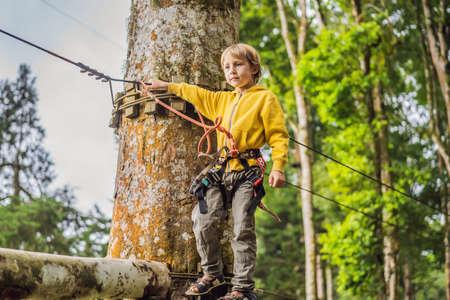 Kleiner Junge in einem Seilpark. Aktive körperliche Erholung des Kindes an der frischen Luft im Park. Training für Kinder Standard-Bild