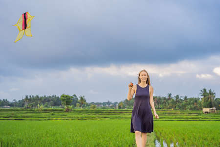Young woman tourist launches a kite in a rice field in Ubud, Bali Island, Indonesia