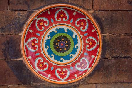 Balinesische Dekoration, bemalte Platte an einer Steinmauer