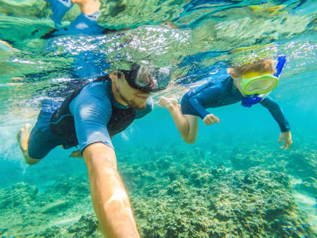 Happy family - active kid in snorkeling mask dive underwater, see tropical fish in coral reef sea pool. Travel adventure, swimming activity on summer beach vacation with child Stock Photo