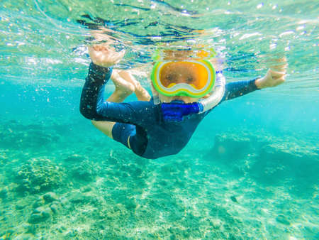 Happy family - active kid in snorkeling mask dive underwater, see tropical fish in coral reef sea pool. Travel adventure, swimming activity on summer beach vacation with child