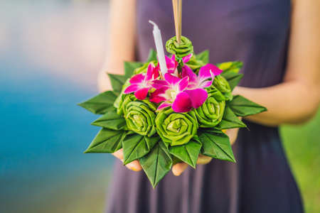 A female tourist holds the Loy Krathong in her hands and is about to launch it into the water. Loy Krathong festival, People buy flowers and candle to light and float on water to celebrate the Loy Krathong festival in Thailand