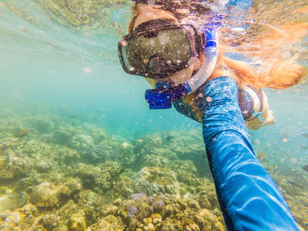 Happy woman in snorkeling mask dive underwater with tropical fishes in coral reef sea pool. Travel lifestyle, water sport outdoor adventure, swimming lessons on summer beach holiday