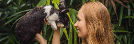 Woman holding a rabbit. Cosmetics test on rabbit animal. Cruelty free and stop animal abuse concept BANNER, LONG FORMAT Stockfoto