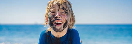 BANNER, LONG FORMAT Black Friday concept. Smiling boy with dirty Black face sitting and playing on black sand sea beach before swimming in ocean. Family active lifestyle, and water leisure on summer vacation with kids. Black Friday, sales of tours and airline tickets or goods