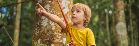 Little boy in a rope park. Active physical recreation of the child in the fresh air in the park. Training for children BANNER, LONG FORMAT Stock Photo