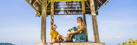 Mom and son in a gazebo in Bali. Traveling with kids concept. Kids Friendly places BANNER, LONG FORMAT