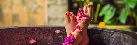 Attractive Young woman in bath with petals of tropical flowers and aroma oils. Spa treatments for skin rejuvenation. Alluring woman in Spa salon. Girl relaxing in bathtub with flower petals. Luxury BA