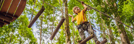 Little boy in a rope park. Active physical recreation of the child in the fresh air in the park. Training for children BANNER, LONG FORMAT Banco de Imagens