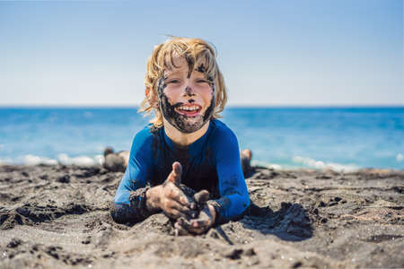 Black Friday concept. Smiling boy with dirty Black face sitting and playing on black sand sea beach before swimming in ocean. Family active lifestyle, and water leisure on summer vacation with kids. Black Friday, sales of tours and airline tickets or goods