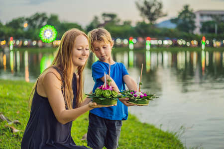Mom and son tourists holds the Loy Krathong in her hands and is about to launch it into the water. Loy Krathong festival, People buy flowers and candle to light and float on water to celebrate the Loy Krathong festival in Thailand