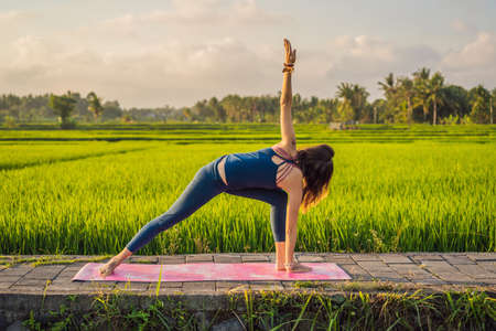 Young woman practice yoga outdoor in rice fields in the morning during wellness retreat in Bali