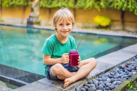 Boy drinks dragon fruit smoothie with steel drinking straw by the pool