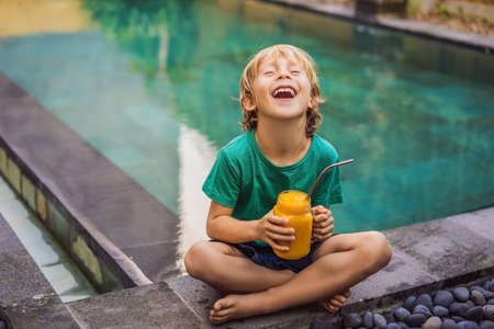 Boy drinking juicy smoothie from mango in glass mason jar with steel straw on the background of the pool. Healthy life concept, copy space 写真素材 - 129984819