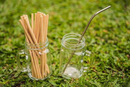 Steel drinking vs disposable straws on grass background. Zero waste concept
