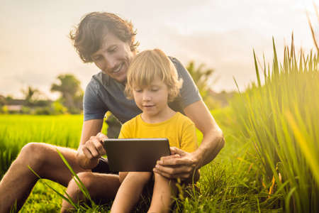 Dad and son sitting on the field holding tablet. Boy sitting on the grass on sunny day. Home schooling or playing a tablet