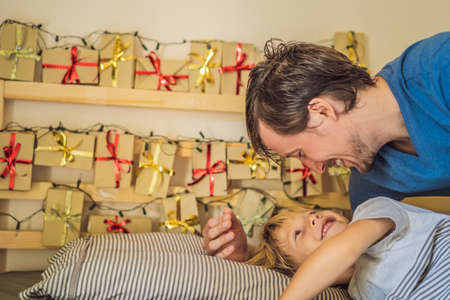 Dad wakes up little boy in the morning and home made advent calendar on a shelf. Winter seasonal tradition. Christmas advent calendar Фото со стока